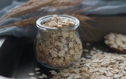 Harina de avena nutritiva sabrosa, tarro de cristal, cuchara de madera y espigas de trigo en el fondo oscuro, foco selectivo Fotos de archivo
