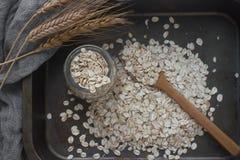 Harina de avena nutritiva sabrosa, tarro de cristal, cuchara de madera y espigas de trigo en el fondo oscuro, visión superior Foto de archivo