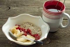 Harina de avena, plátano y fresas congeladas en el cuenco y la taza blancos de Foto de archivo