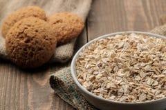 Harina de avena y galletas de harina de avena secas en un cuenco blanco Alimento Alimento sano En una tabla de madera marrón fotos de archivo libres de regalías