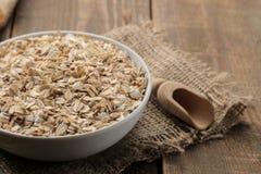 Harina de avena y galletas de harina de avena secas en un cuenco blanco y una cuchara de madera Alimento Alimento sano En una tab foto de archivo libre de regalías