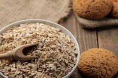Harina de avena y galletas de harina de avena secas en un cuenco blanco y una cuchara de madera Alimento Alimento sano En una tab imagenes de archivo