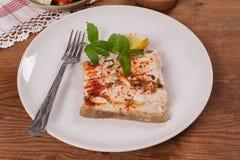Harina de pescado asada del siluro con el limón en una placa blanca Fotos de archivo