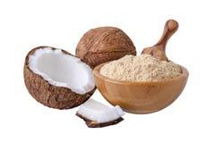 Harina del coco en cuenco de madera con una cucharada aislada en blanco Foto de archivo