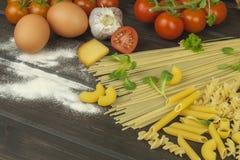 Harina derramada Pastas y verduras en una tabla de madera Fotografía de archivo libre de regalías