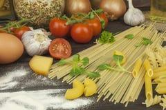 Harina derramada Pastas y verduras en una tabla de madera Foto de archivo