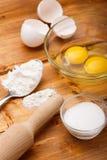 Harina, huevos y sal en la tabla de madera fotografía de archivo