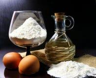 harina Producto alimenticio El proceso de preparar la pasta eggshell Petróleo de coco Harina en un vidrio Harina derramada Aceite imagen de archivo