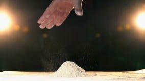 Harina que lanza de la mano en un rapid del montón La mano lanza la montaña blanca MES lento del polvo metrajes