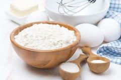 Harina, sal, azúcar y huevos para las crepes que cuecen en la tabla de madera fotos de archivo