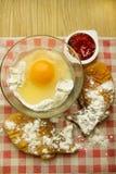 Harina y huevo en la tabla con las tortas Imagen de archivo libre de regalías