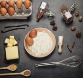 Harina y huevos en cuenco, comidas y especias en la mesa, en gris fotos de archivo libres de regalías