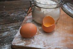 Harina y huevos en un tablero de madera Foto de archivo libre de regalías