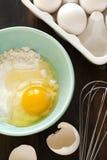 Harina y huevos en una tabla de madera Foto de archivo