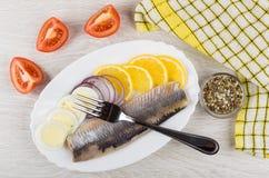 Haringen met citroen, ui, ei, tomaat, specerij, servet en FO stock foto's