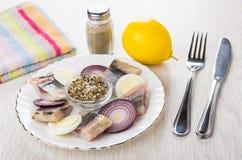 Haringen met eieren, specerij, ui in plaat, citroen, peper, kni stock afbeeldingen