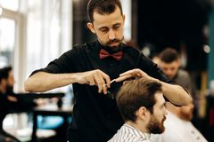 Harismatic barber with mustache dressed in a black shirt with a red bow tie scissors the hair of a young man in a stock image