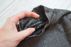 HARKÌV, UCRAINA - 11 AGOSTO 2017: Etichetta nera New Look su un bordo grigio in una mano femminile Primo piano Immagine Stock
