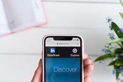 HARK?V, UCRAINA - 10 aprile 2019: IPhone X di Apple in mano femminile con slideshare sito netto sullo schermo fotografie stock libere da diritti