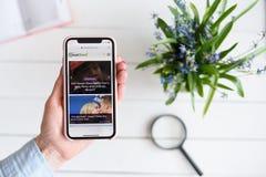 HARK?V, UCRAINA - 10 aprile 2019: La donna tiene il iPhone X di Apple con cheatsheet sito di COM sullo schermo immagini stock libere da diritti