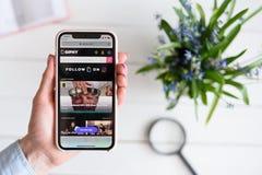 HARK?V, UCRAINA - 10 aprile 2019: La donna tiene il iPhone X di Apple con giphy sito di COM sullo schermo fotografia stock
