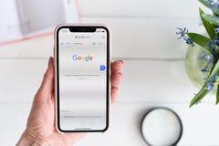HARK?V, UCRAINA - 10 aprile 2019: La donna tiene il iPhone X di Apple con Google sito di COM sullo schermo Pagina di ricerca fotografia stock