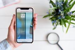 HARK?V, UCRAINA - 10 aprile 2019: La donna tiene il iPhone X di Apple con i twentytwowords sito di COM sullo schermo fotografia stock