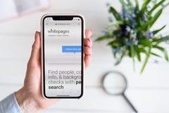 HARK?V, UCRAINA - 10 aprile 2019: La donna tiene il iPhone X di Apple con i white pages sito di COM sullo schermo immagini stock libere da diritti