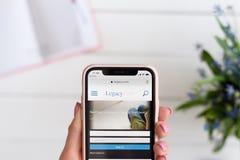 HARK?V, UCRAINA - 10 aprile 2019: La donna tiene il iPhone X di Apple con l'eredit? sito di COM sullo schermo immagine stock libera da diritti