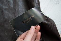 HARKÌV, UCRAINA - 27 SETTEMBRE 2017: Etichetta nera Zara Basic in una mano femminile Primo piano Fotografie Stock Libere da Diritti