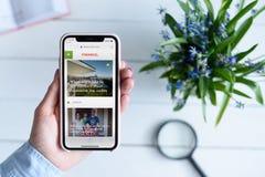 HARK?V, UCRAINA - 10 aprile 2019: IPhone X di Apple in mano femminile con finance101 sito di COM sullo schermo immagine stock