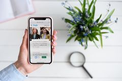 HARK?V, UCRAINA - 10 aprile 2019: La donna tiene il iPhone X di Apple con la gente sito di COM sullo schermo fotografie stock libere da diritti