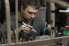 HARK?V, UCRAINA - 31 gennaio 2019: Il gioielliere matrice tiene l'attrezzo in sue mani e fa i gioielli nel suo luogo di lavoro fotografie stock libere da diritti
