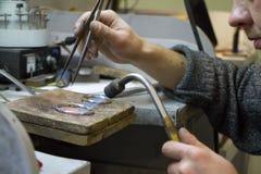 HARK?V, UCRAINA - 31 gennaio 2019: Il gioielliere matrice tiene l'attrezzo in sue mani e fa i gioielli nel suo luogo di lavoro immagini stock