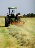 Harken des Grases mit Traktor Stockfotografie