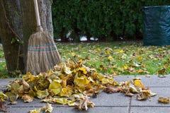 Harken des Herbstlaubs mit einem Besen stockfotos