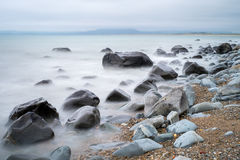 Harlech coastline. Rocks on the coastline of Harlech, Wales. The background has the Snowdonia mountain range just covered by cloud Stock Image