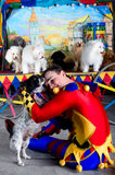Harlekin umfaßt kleinen Hund Stockfotografie