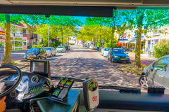 Harlem, Amsterdam, Netherlands - July 14, 2015: Inside public transportation bus in traffic, front seat view, driver on Royalty Free Stock Photography