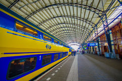 Harlem, Amsterdam, Netherlands - July 14, 2015: Inside railroad station, large roof covering platform, blue and yellow Royalty Free Stock Images