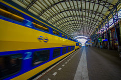 Harlem, Amsterdam, Netherlands - July 14, 2015: Inside railroad station, large roof covering platform, blue and yellow Stock Images
