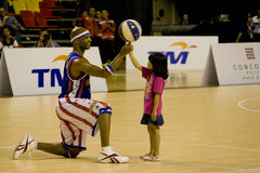 Harlem Globetrotters Basketball Action. Image of Flight Time Lang of the world famous Harlem Globetrotters basketball team entertaining a small kid during the Stock Photos