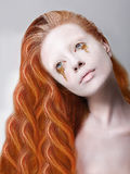 Harlequin. Artistic Red Hair Woman with Painted Face and Creative Makeup Royalty Free Stock Photo