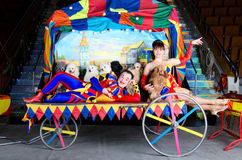 Harlequin and Colombina. Couple of smiling clowns posing with small dogs on vintage carriage with the painting of the old town Royalty Free Stock Image