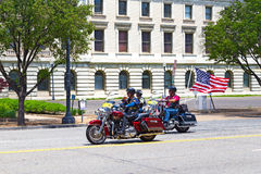 Harley Davidson colorful motorcycles travel on Independence Avenue under American flag. Royalty Free Stock Image