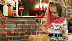 Harley quinn που διακοσμεί την κολοκύθα με τα γλυκά, κοστούμι αποκριών, επικίνδυνο παιδί, κόμμα αποκριών απόθεμα βίντεο
