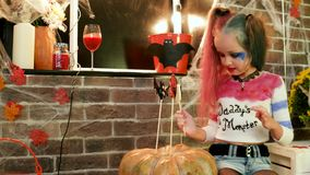 Harley quinn decorating pumpkin with sweets, halloween costume, dangerous child, halloween party stock video footage