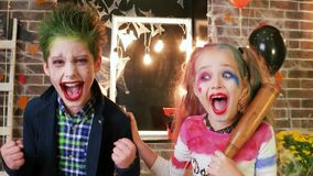 Harley quinn and joker screaming, kids having fun at halloween party, crazy character, spooky makeup stock video footage