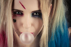 Harley Quinn makeup. Cosplayer girl in Harley Quinn makeup and costume making bubble Royalty Free Stock Images