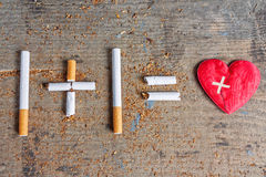 Harm of smoking. Diseased heart. Antismoking background. Cigarettes and diseased heart on wooden surface royalty free stock image